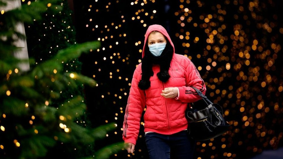 Woman in a mask walks past Christmas decorations