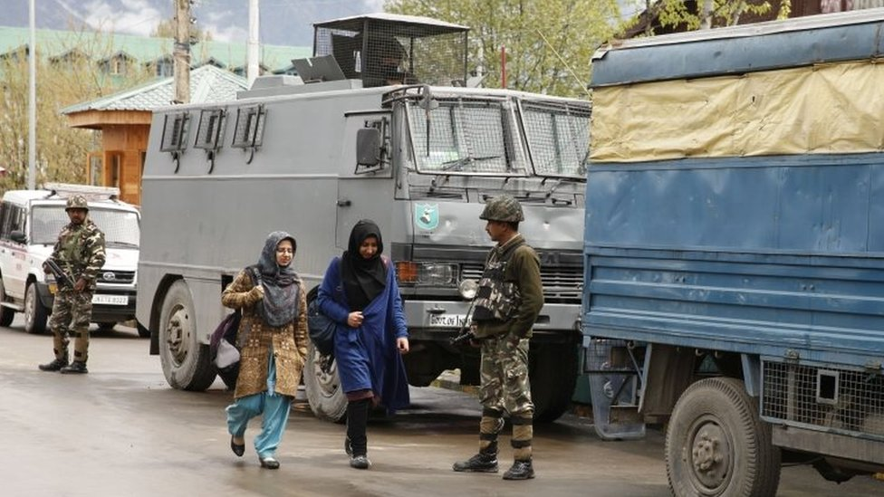Students walk past an Indian paramilitary soldiers of Central Reserve Police Force (CRPF) at the National Institute of Technology (NIT) in Srinagar, summer capital of Indian administered Kashmir,