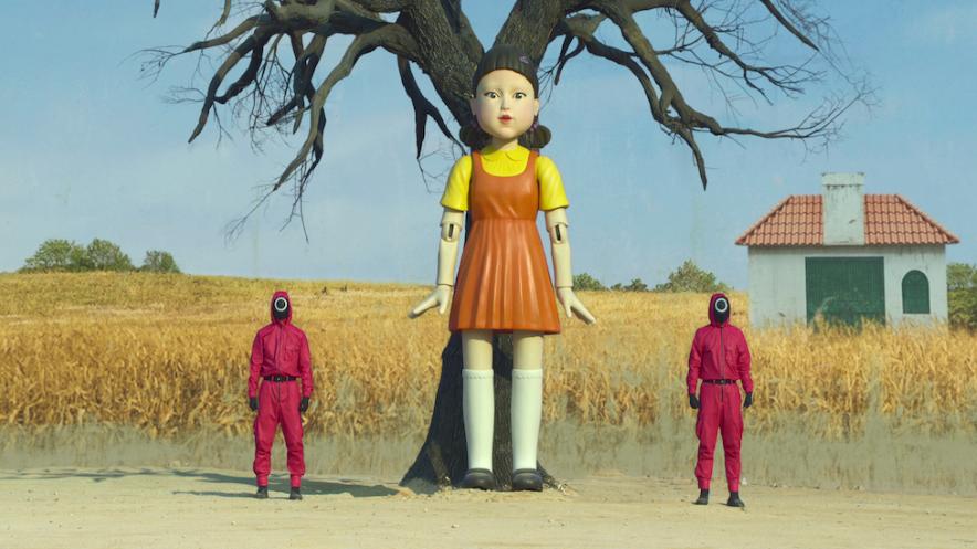 """Una de las escenas de """"El juego del calamar"""" que muestra a dos personajes junto a una muñeca que busca jugadores que se mueven para activar ejecuciones automáticas."""