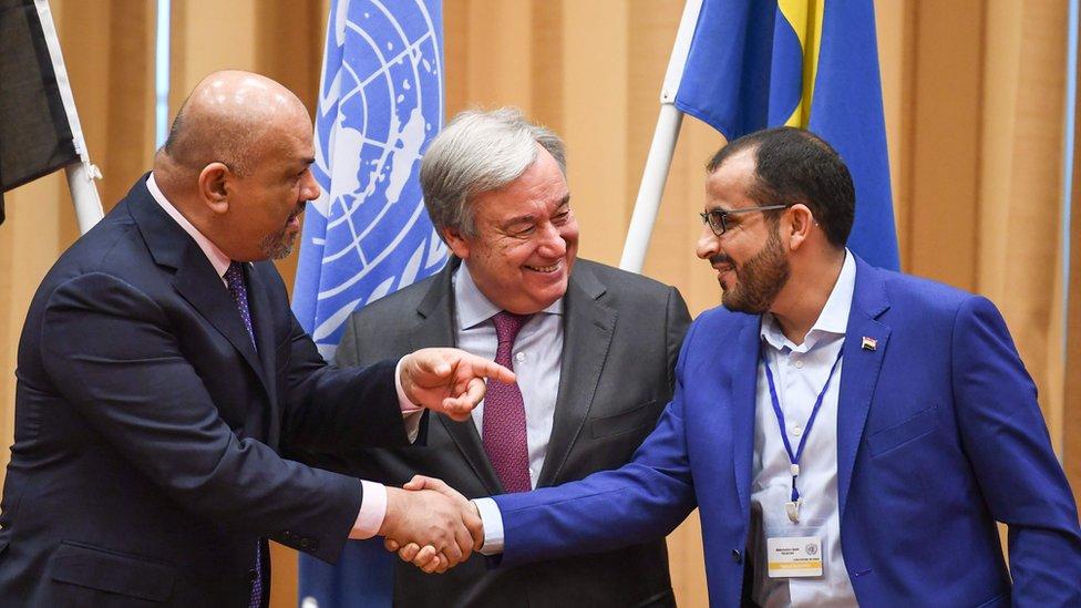 ممثل الحكومة اليمنية المعترف بها دوليا وممثل الحوثيين يتصافحان في ختام جولة تفاوض كللت باتفاق وقف اطلاق نار في مدينة الحديدة برعاية الأمم المتحدة