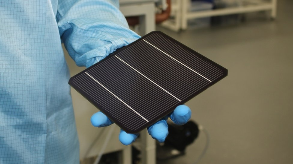 Solar panel about the size of a tablet being held in a lab