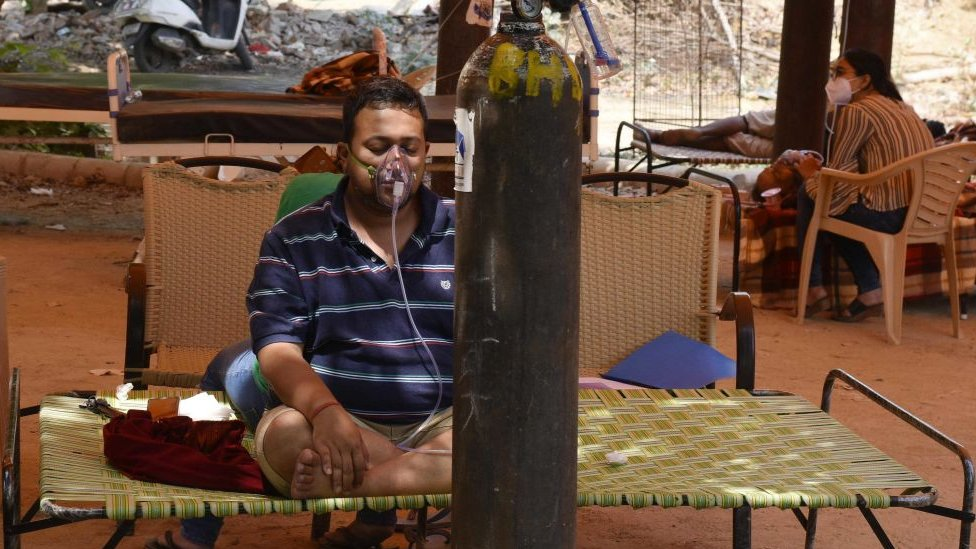 Hombre en India siendo asistido por un tanque de oxígeno.