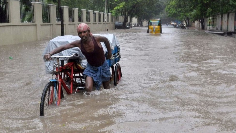 An Indian labourer pushes his cycle trishaw through floodwaters in Chennai on December 1, 2015,