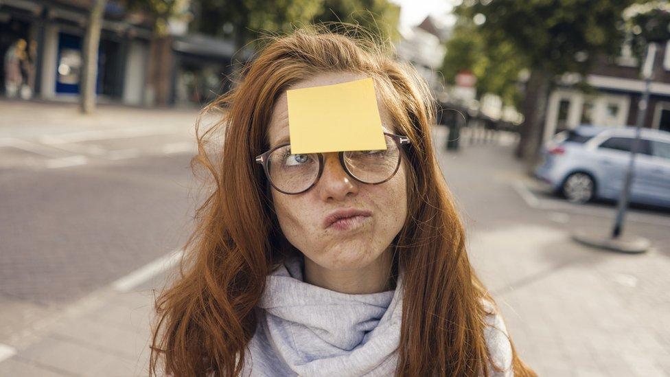 Mulher com post-it em branco colado na testa