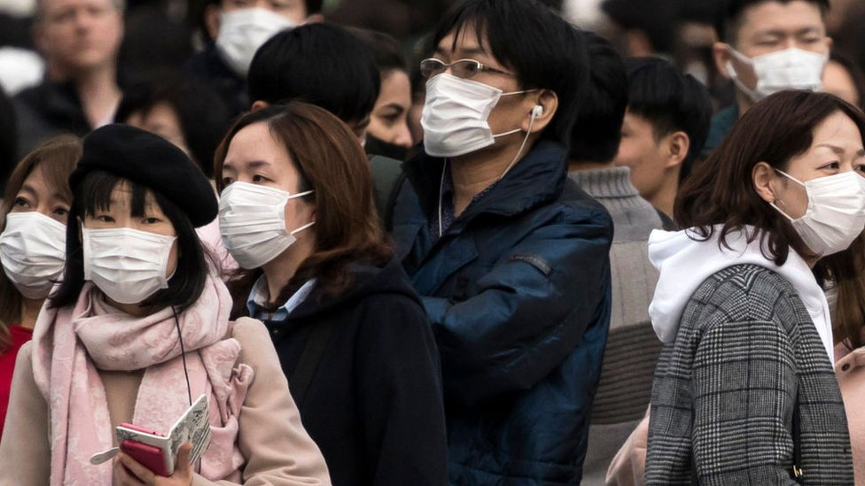 People wearing masks wait to cross a road in the Shibuya district in Tokyo, Japan.