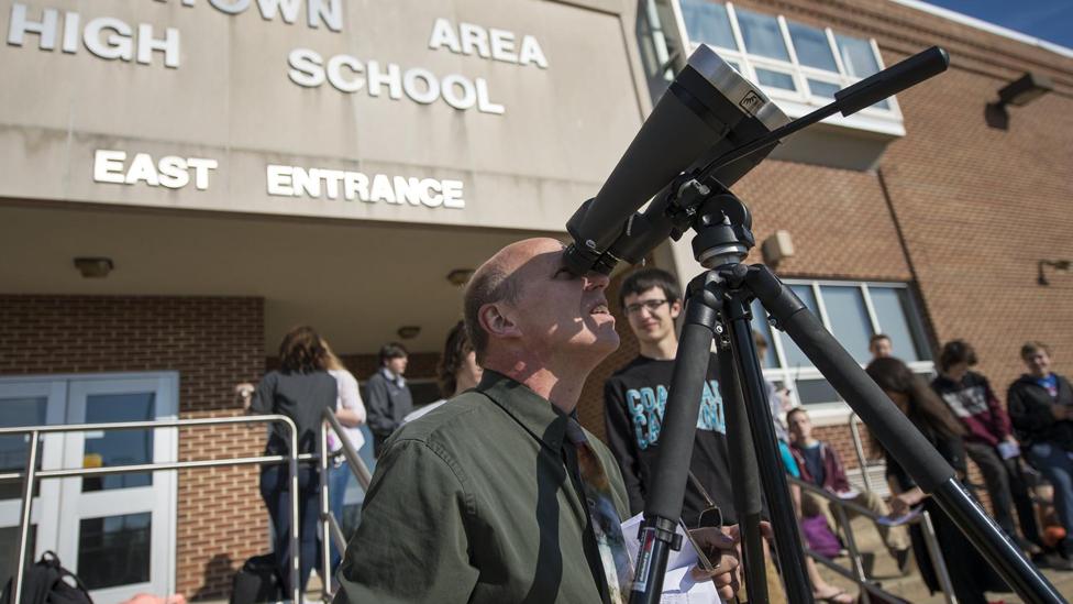 Un hombre observa el tránsito de Mercurio en 2016 con binoculares que tiene un filtro solar antepuesto al objetivo