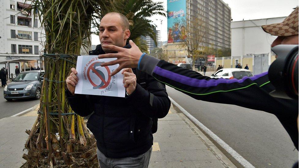 """صورة لرجل يحمل لافتة للتعبير عن رفضة للـ""""عهدة الخامسة"""" و""""شرطي في زي مدني"""" يحاول انتزاعها"""