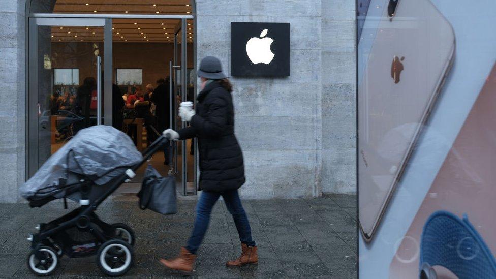 Mujer pasea frente a tienda de Apple
