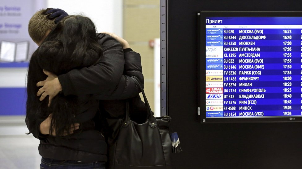 A couple hug each other next to a flight information board at Pulkovo airport in St Petersburg, Russia (31 October 2015)