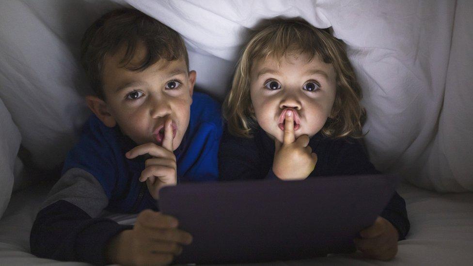 Dos niños con el gesto de silencio.