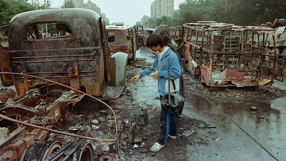 Un ciudadano chino observa los escombros de vehículos quemados tras los enfrentamientos en la Plaza de Tiananmen