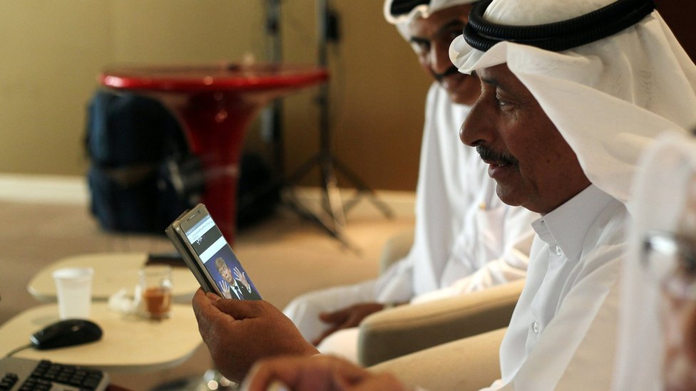 File photo showing a trader using his phone to follow news of the US presidential election result in Doha, Qatar (9 November 2016)