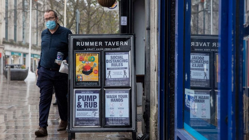 A man walks past a pub sign in Cardiff displaying social distancing notices