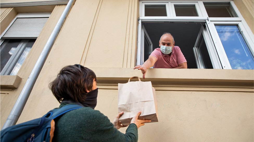 Mujer da bolsa de comida a un hombre