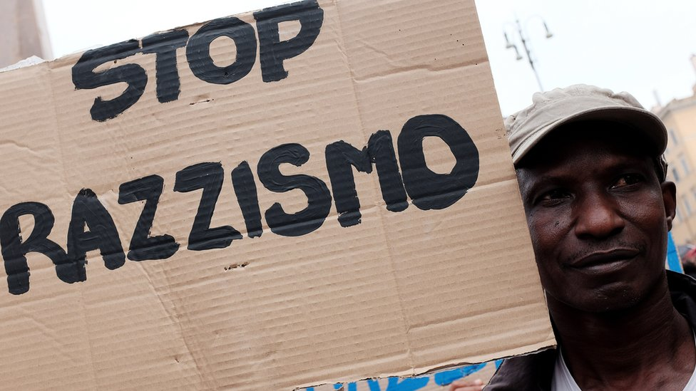 A migrant holds a placard reading 'stop racism' during a demonstration in Rome on 16 June, 2015