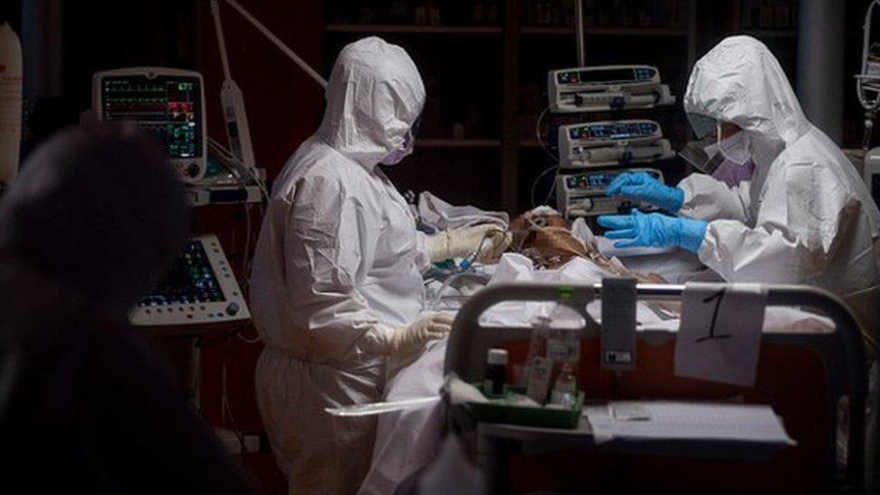 Médicos en un hospital totalmente protegidos atendiendo a un paciente.