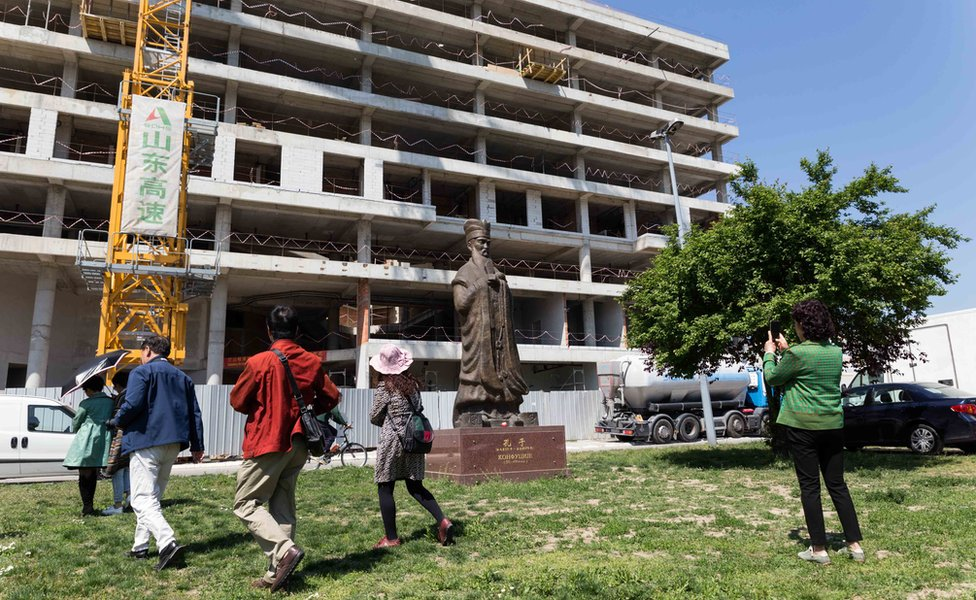 Chinese tourists walk past a Confucius statute outside the former Chinese embassy site