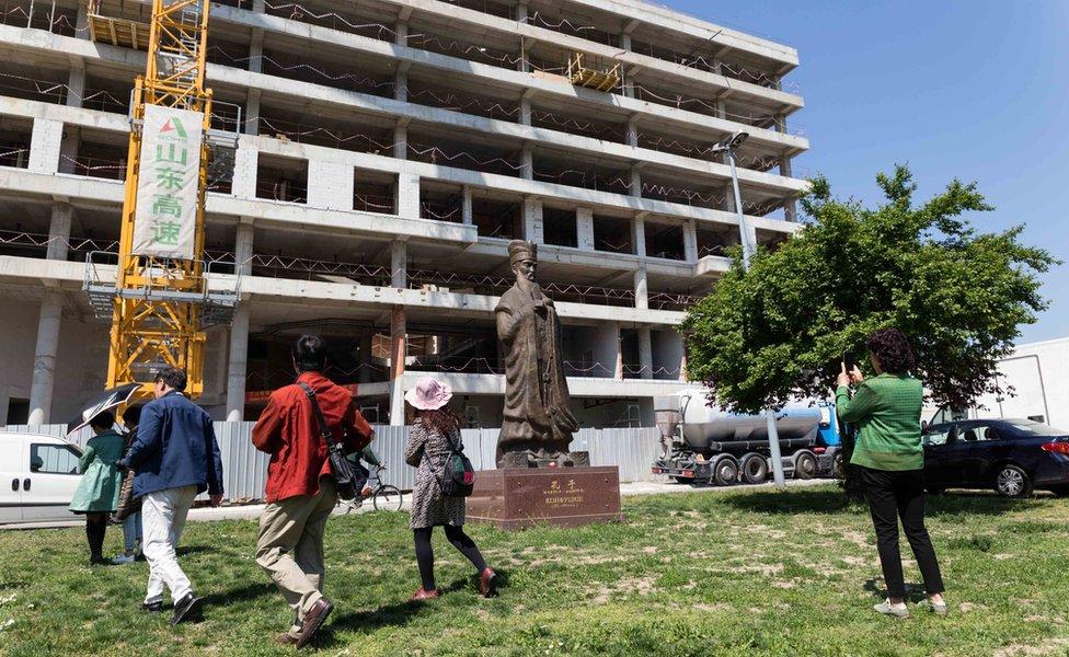 Turistas ven una estatua de Confucio.