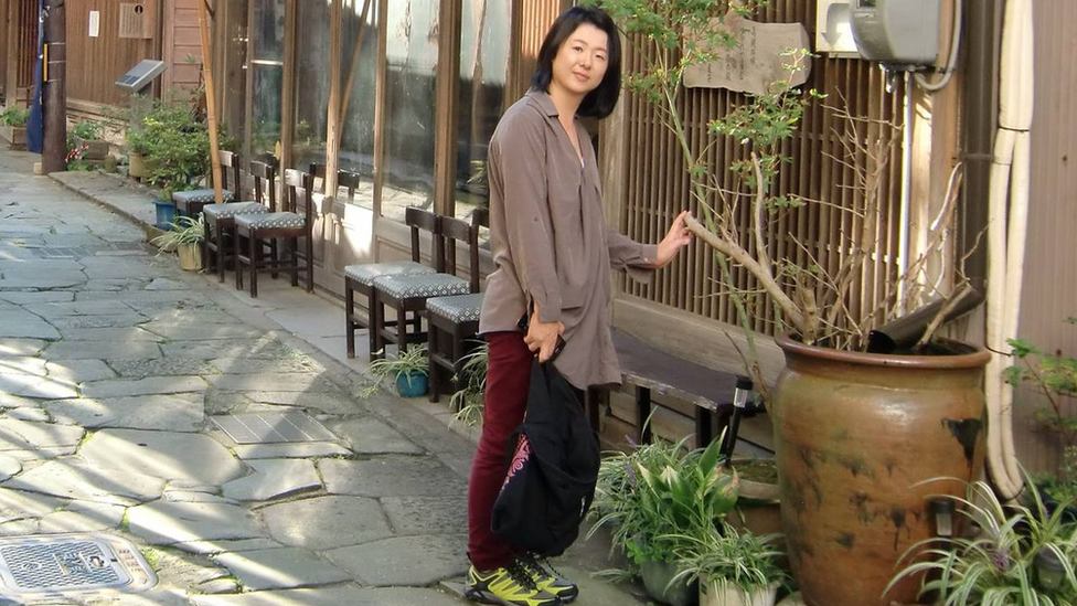 Eriko Kobayashi poses for a picture on a Japanese street