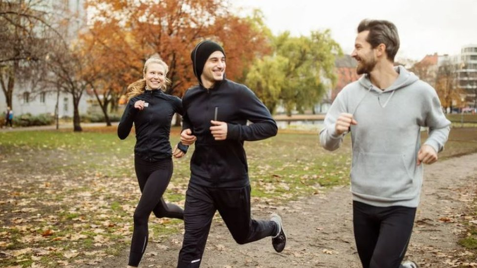 Three people running in a park
