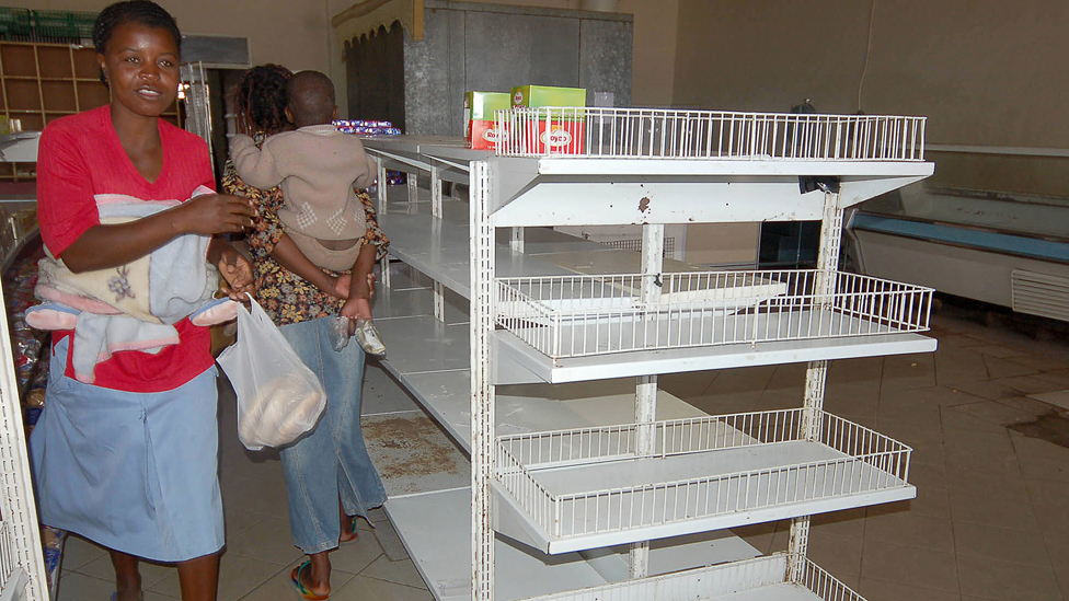 Harare shoppers walk past empty shelves in 2007