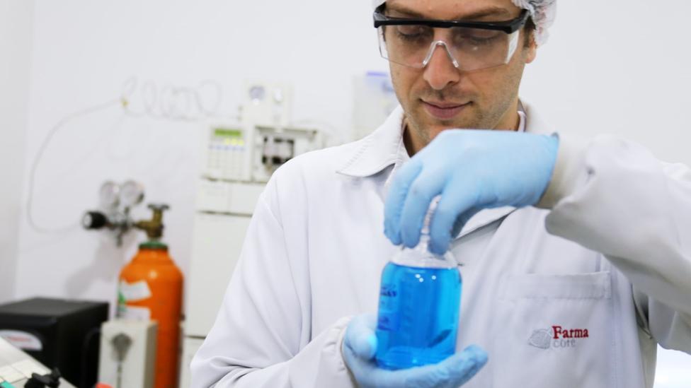 Técnico de laboratório mexe com substâncias num recipiente