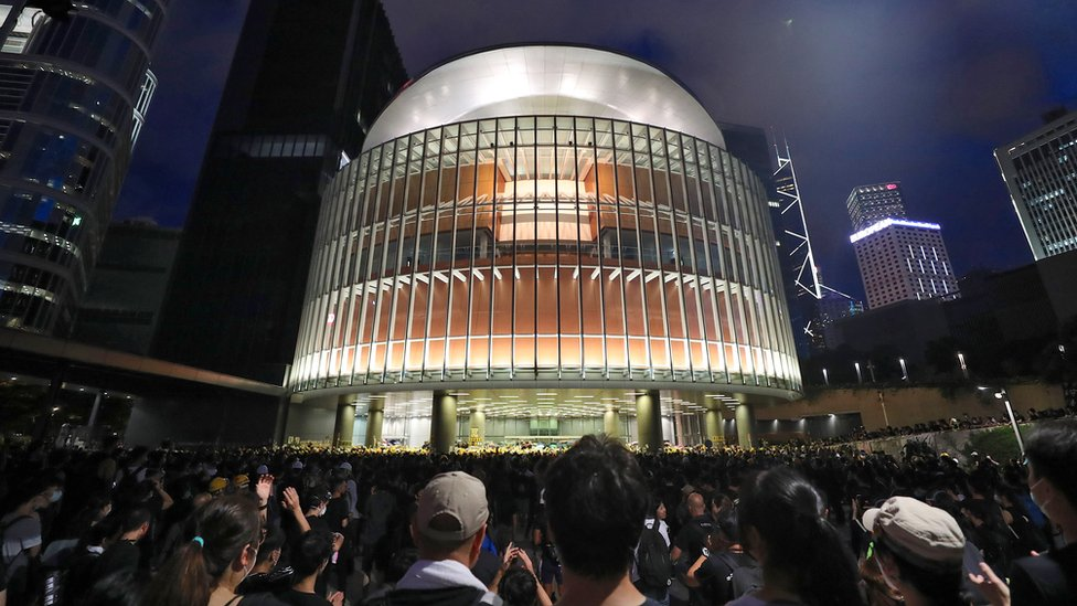 An illuminated modern building of steel and glass, circular at the front, is seen against a dark sky, with innumerable people watching it passively from a distance