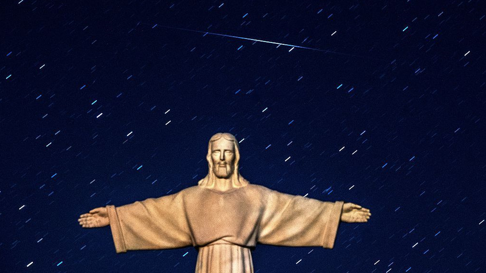 A Perseid meteor crosses the night sky over a statue of Jesus Christ in the village of Ivye some 125 km west of Minsk, on 13 August 2016.