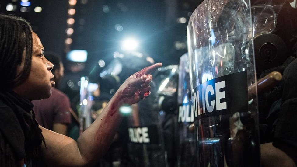 A Black Lives Matter protester faces a line of riot police