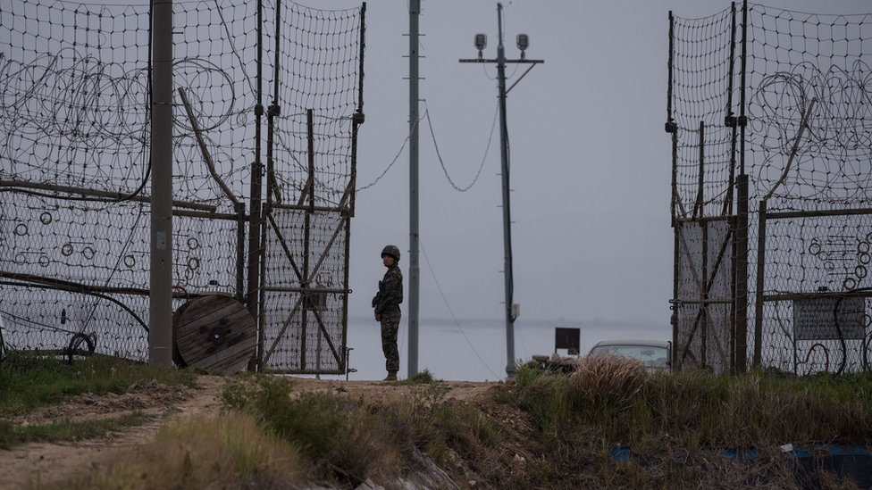 A soldier stands guard at an opening in a fence at the DMZ