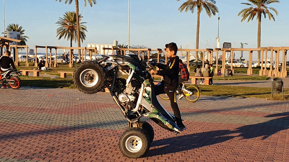 A Libyan boy performs a wheel-stand manoeuvre with an all-terrain vehicle at a park in the capital Tripoli on 31 January 2020