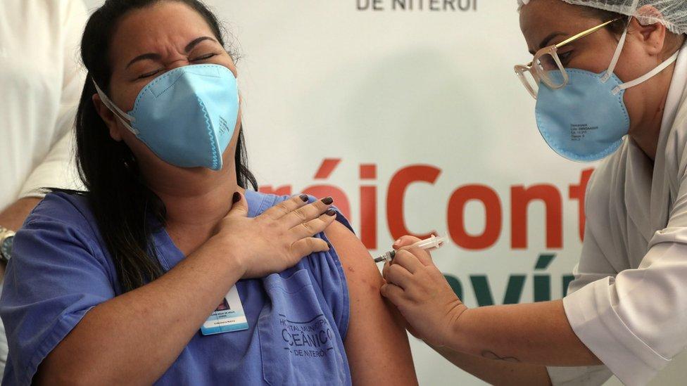 Mulher de cabelo preto comprido, pela parda e uniforme de profissional de saúde recebe vacina no Rio de Janeiro