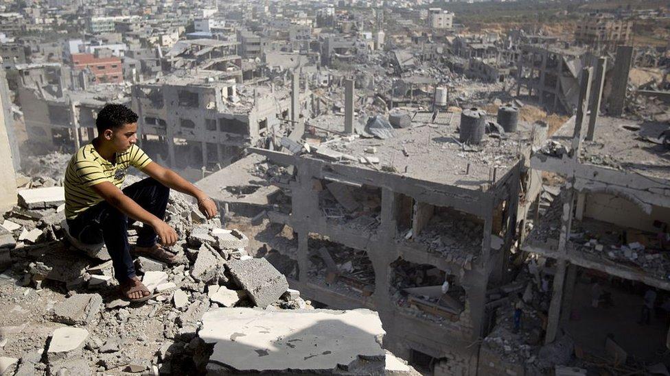 طفل يجلس فوق منزل مدمر