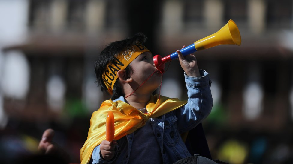 A child plays a vuvuzela at the homecoming party for Egan Bernal