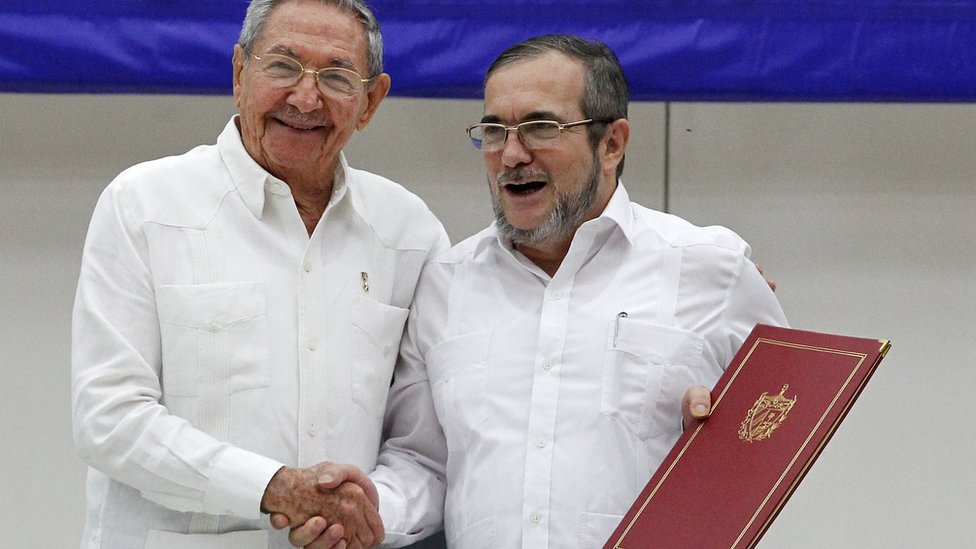"""Raul Castro President of Cuba (L) and Timoleon Jimenez """"Timonchenko"""" (R) shake hands during a meeting to announce the Ceasefire Agreement between Colombian Government and the FARC rebels on June 23, 2016 in Havana, Cuba"""