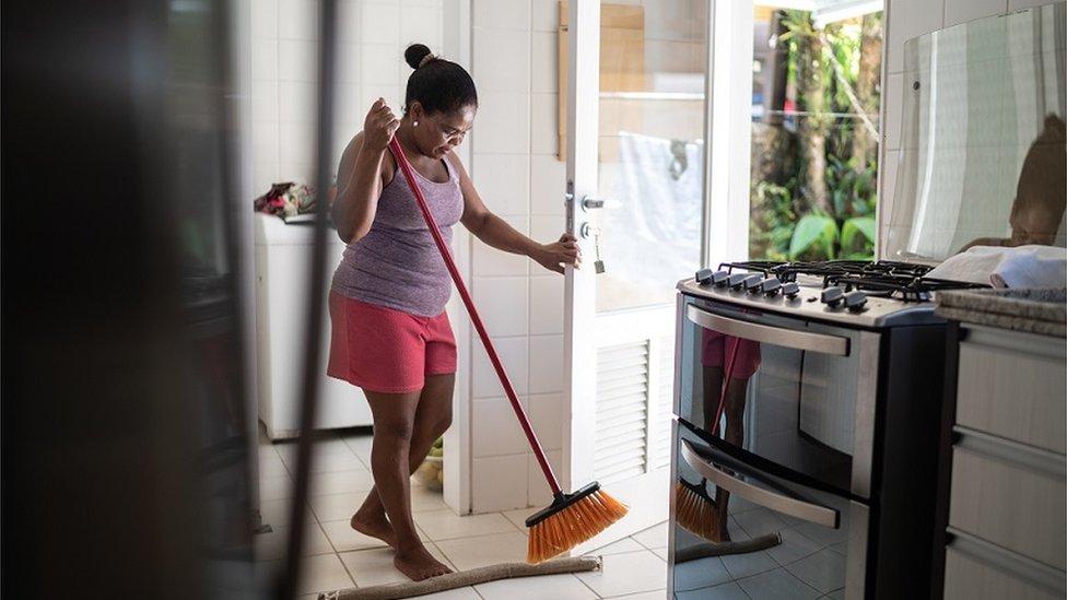 Mulher negra descalça varrendo o chão de uma cozinha