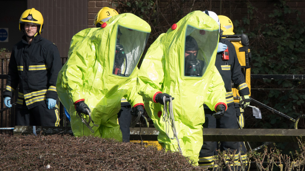 Specialist officers in protective suits prepare to secure the police forensic tent that had been blown over by the wind and is covering the bench where Sergei Skripal was found critically with his daughter on March 4