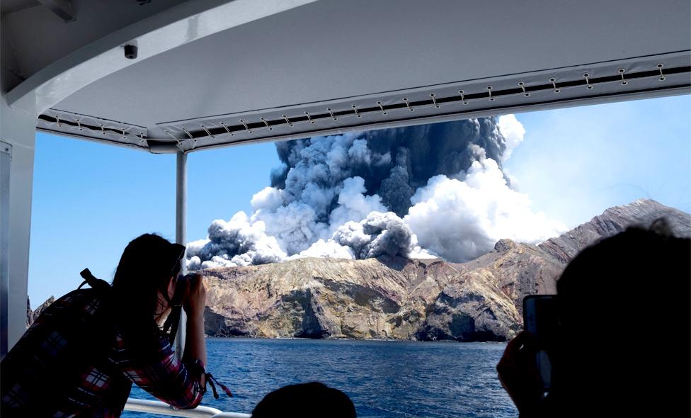 Turistas viendo y fotografiando desde un bote el volcán en plena erupción.