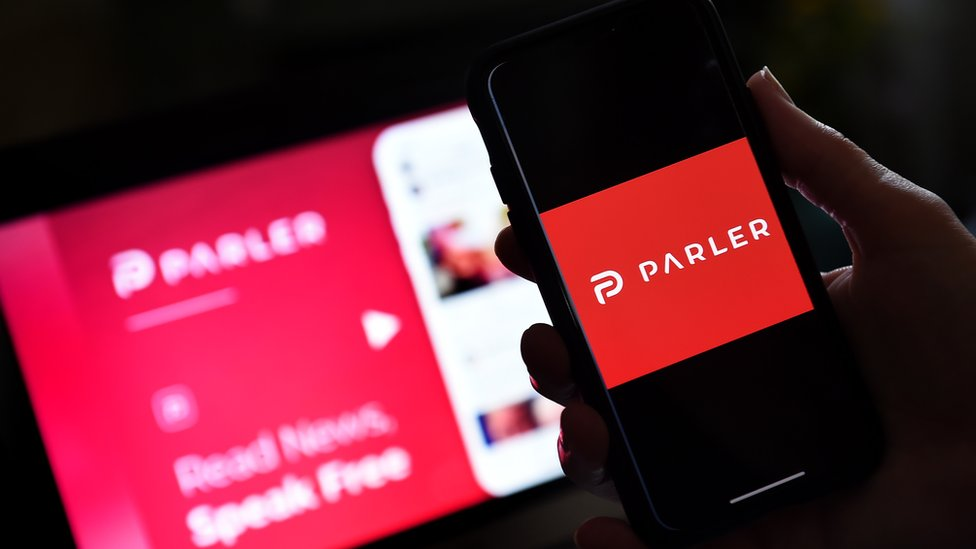A photo illustration shows someone holding a phone with the Parler logo on it, while a laptop screen with its advertising is seen blurred in soft focus in the background