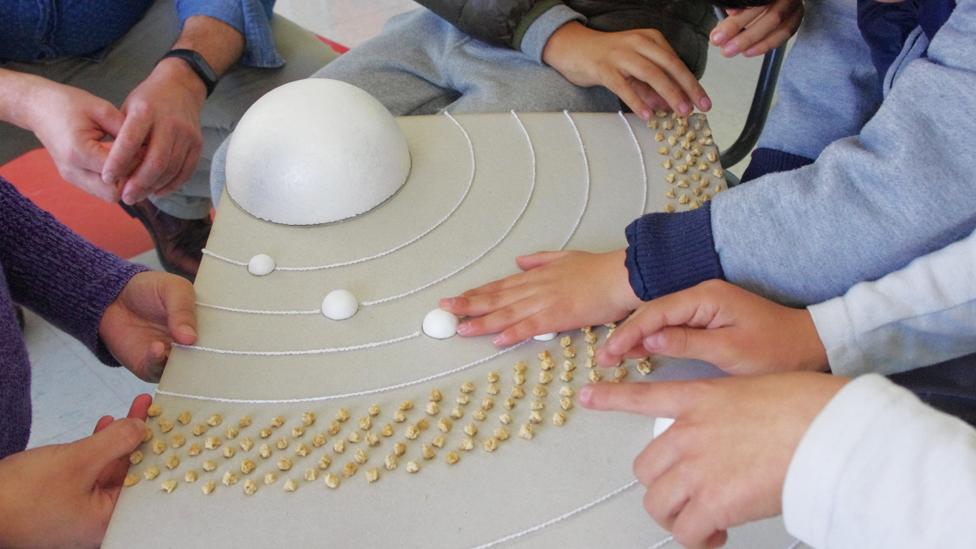 Niños tocando una maqueta que representa las órbitas de los planetas