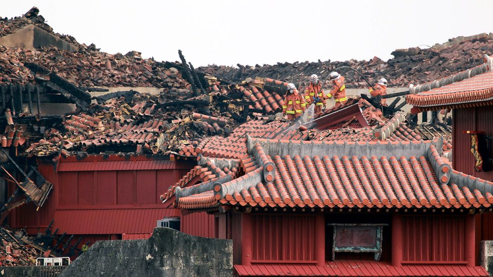 Firefighters inspect the heavily damaged Shuri Castle in Naha
