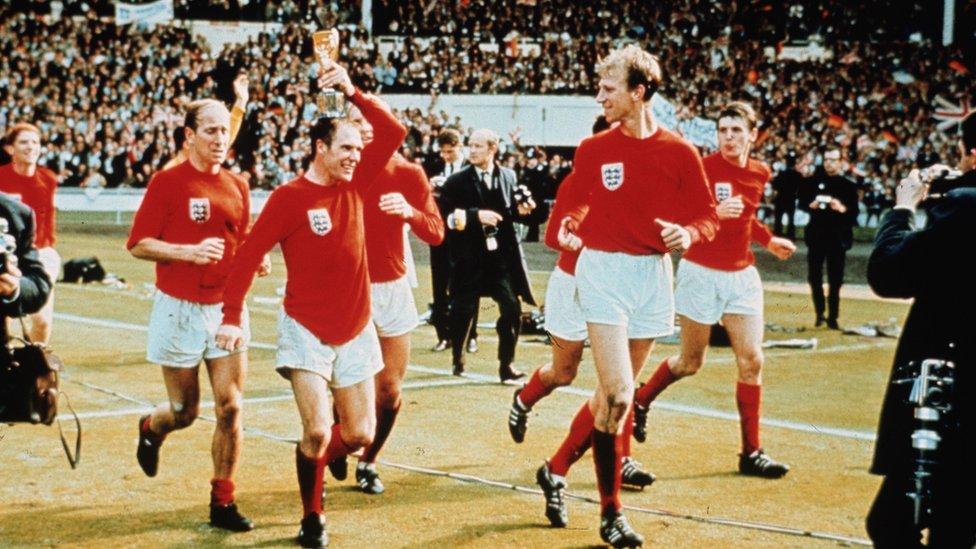 Jack Charlton observa a Ray Wilson posando la Copa Jules Rimet sobre su cabeza, mientras Bobby Charlton los sigue en la vuelta de honor en Wembley en 1966.