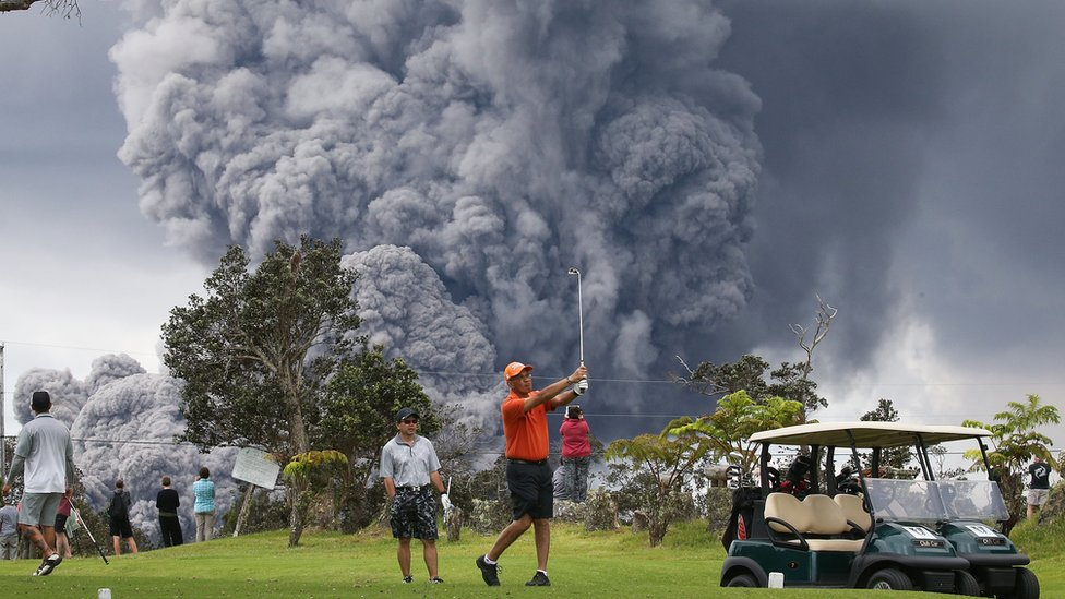 A man plays golf with a cloud from Kilauea behind him