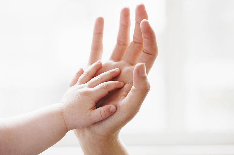 Una mano de una mujer y una mano de un bebé