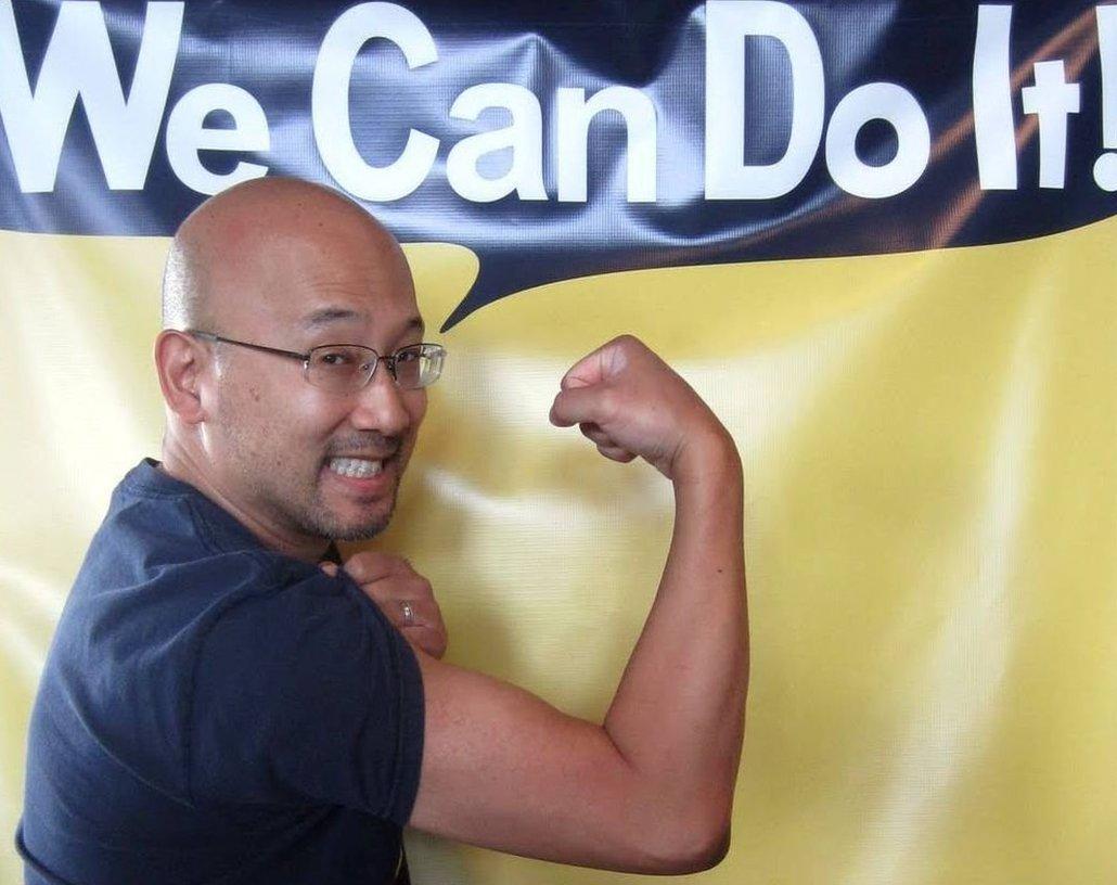 """Eugene Hung fléchissant ses muscles sous une bannière disant : """"Nous pouvons le faire !"""""""