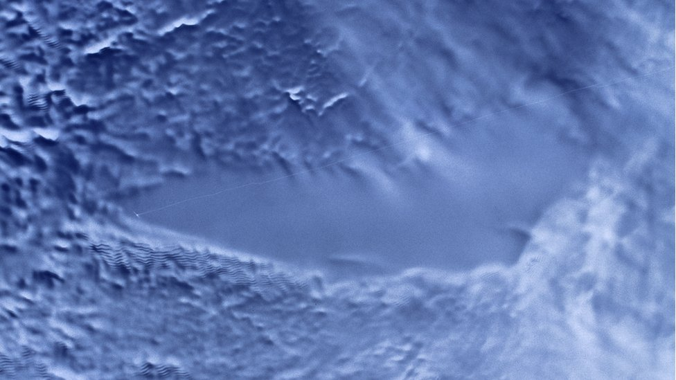 Satellite image of a flat region of ice, surrounded by more textured terrain