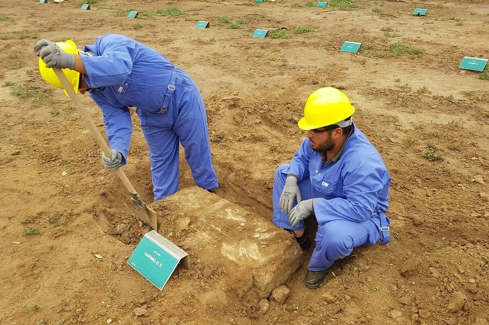 Two men working in blue boiler suits and yellow hard hats to restore graves in Iraq