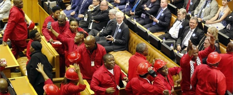 Julius Malema, center, leader of the Economic Freedom Fighters political party leaves the inside of parliament with his members as President Jacob Zuma attempts to give his state of the nation address in Cape Town, South Africa, Thursday, Feb. 11, 2016.