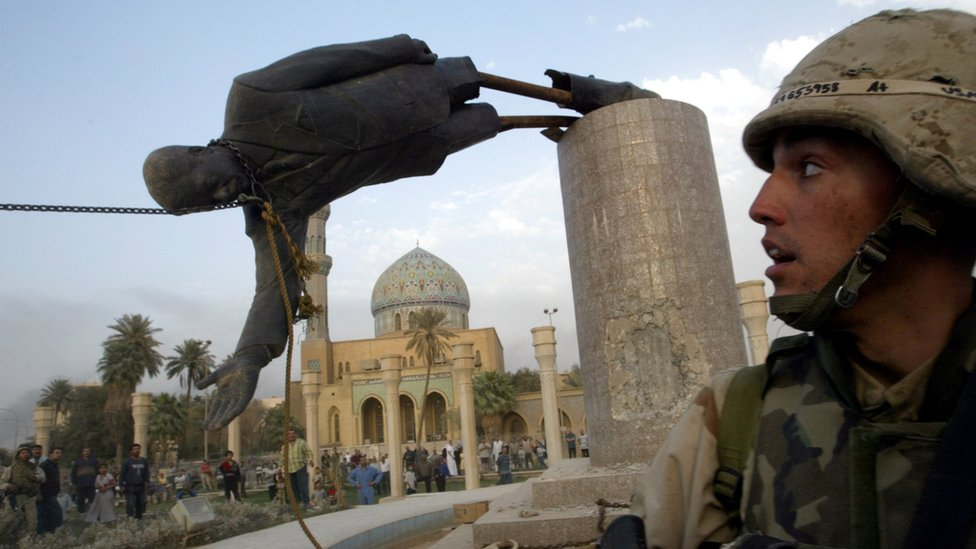 A US soldier watches as a statue of ousted Iraqi President Saddam Hussein is pulled over in Baghdad, Iraq (9 April 2003)