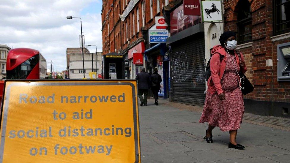 Woman walking on High Street wearing face mask